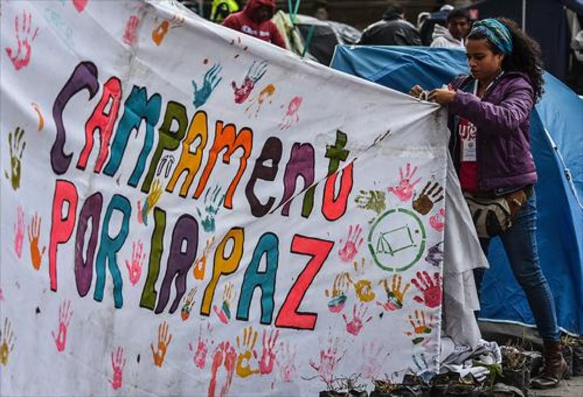 Una joven ayuda a colocar una pancarta a favor del acuerdo de paz en una acampada en Bogotá.