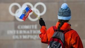 Una mujer ondea una bandera rusa ante la sede del COI en Lausana, este martes.