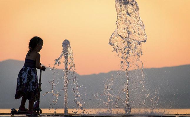 Una niña se refresca en una fuente.
