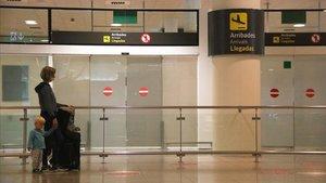 Una pasajera esperando en la terminal del aeropuerto de El Prat, este domingo.