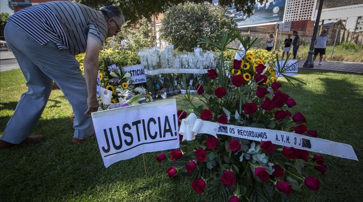 Un miembro de la Asociación de Víctimas del Metro 3 de Julio deja un ramo de flores junto al monumento que recuerda a las 43 víctimas mortales del accidente.