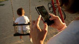 Una madre atiende una llamada delante de su hijo.