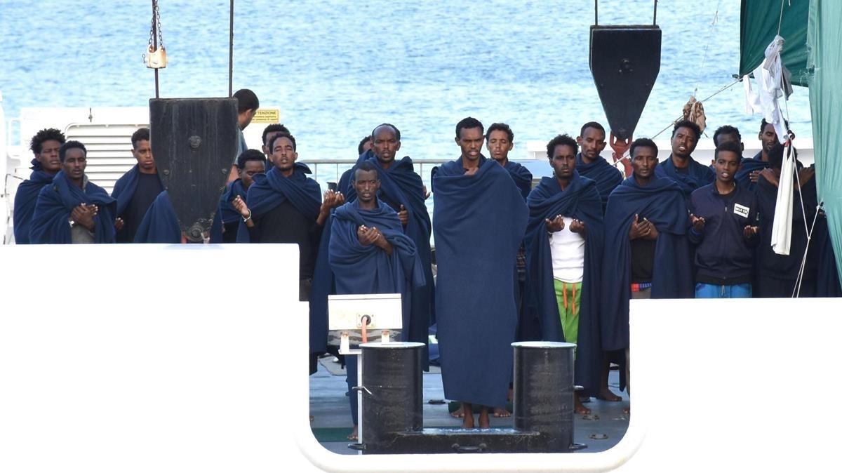 Un grupo de personas reza a bordo del Diociotti, atracado desde hace unos días en el puerto de Catania (Sicilia).
