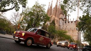 Dos 600 de la comitiva 'vintage' circulan delante de la Sagrada Família al comienzo del 'night tour' de Trip Troop Vintage Tours.