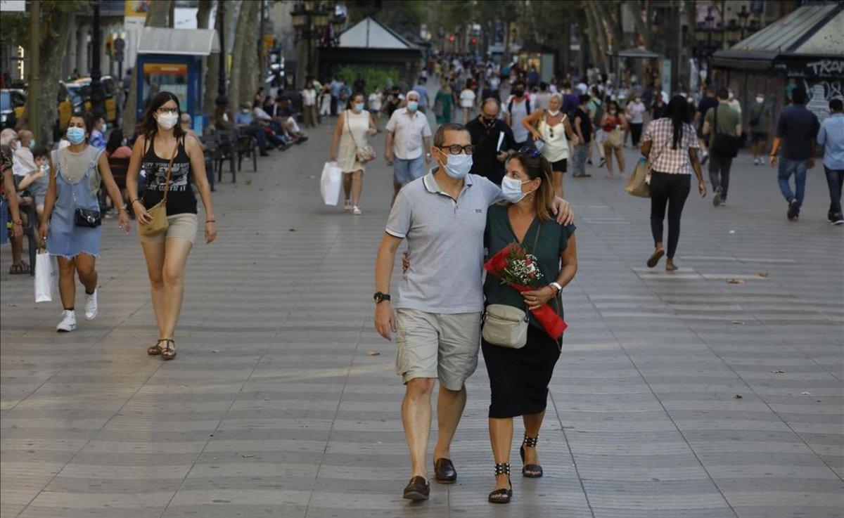 Gente con mascarilla pasea por la Rambla de Barcelona.
