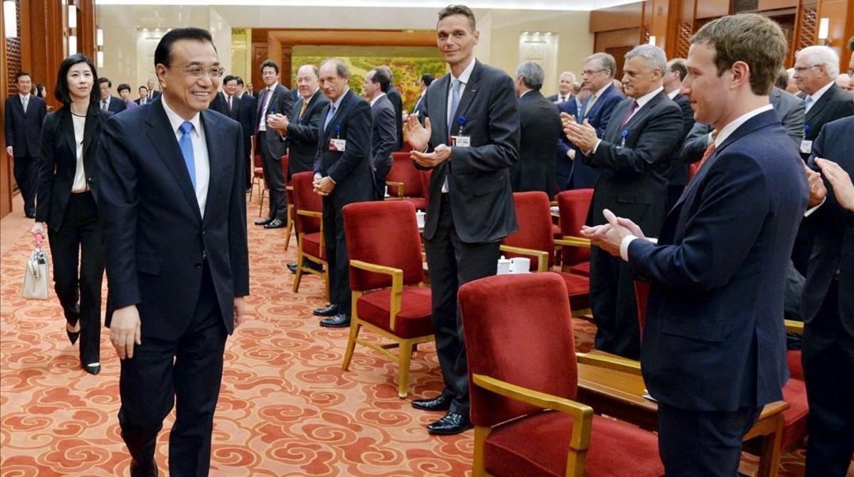 Zuckerberg (derecha) aplaude a la llegada del primer ministro chino, Li Keqiang, en una reunión empresarial en Pekín, el 21 de marzo.