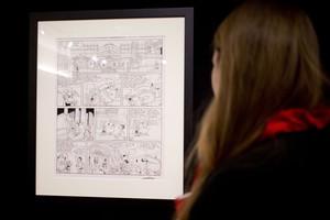 Una mujer mira la plancha de Astérix subastada a beneficio de los familiares de los dibujantes de Charlie Hebdo.