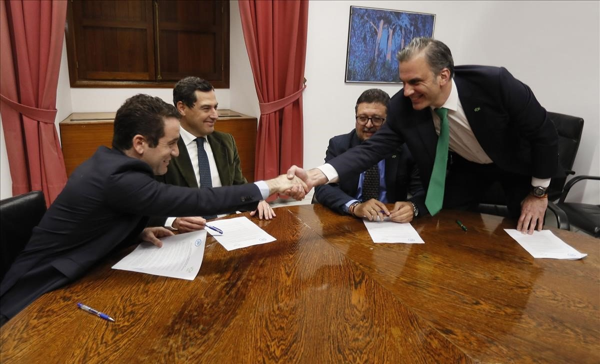 Los secretarios generales del PP, Teodoro García Egea, y de Vox, Francisco Javier Ortega Smith, estrechan las manos delante de los líderes andaluces del PP, Juanma Moreno y de Vox, Francisco Serrano, durante una reunión esta tarde en el Parlamento de Andalucía.