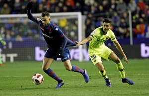 Levante defender Borja Mayora, left, duels for the ball with Barcelonas Chumi during the la Copa del Rey round of 16 first leg soccer match between Levante and Barcelona at the Ciutat de Valencia stadium in Valencia, Spain, Thursday Jan. 10, 2019. (AP Photo/Alberto Saiz)