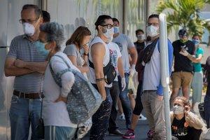 Decenas de personas con tapabocas hacen fila este para abastecerse de medicamentos y productos de higiene personal en una farmacia de Caracas.