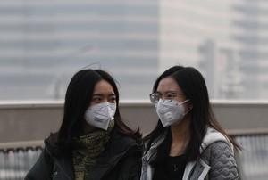Dos chicas se protegen de la contaminación en Pekín, en una imagen de archivo.