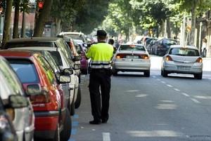 Un empleado de BSM impone una sanción a un vehículo aparcado en el áreaazul de la calle de Girona.