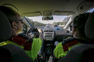 Dos mossos en un coche camuflado en la autopista A-2, el mes pasado.