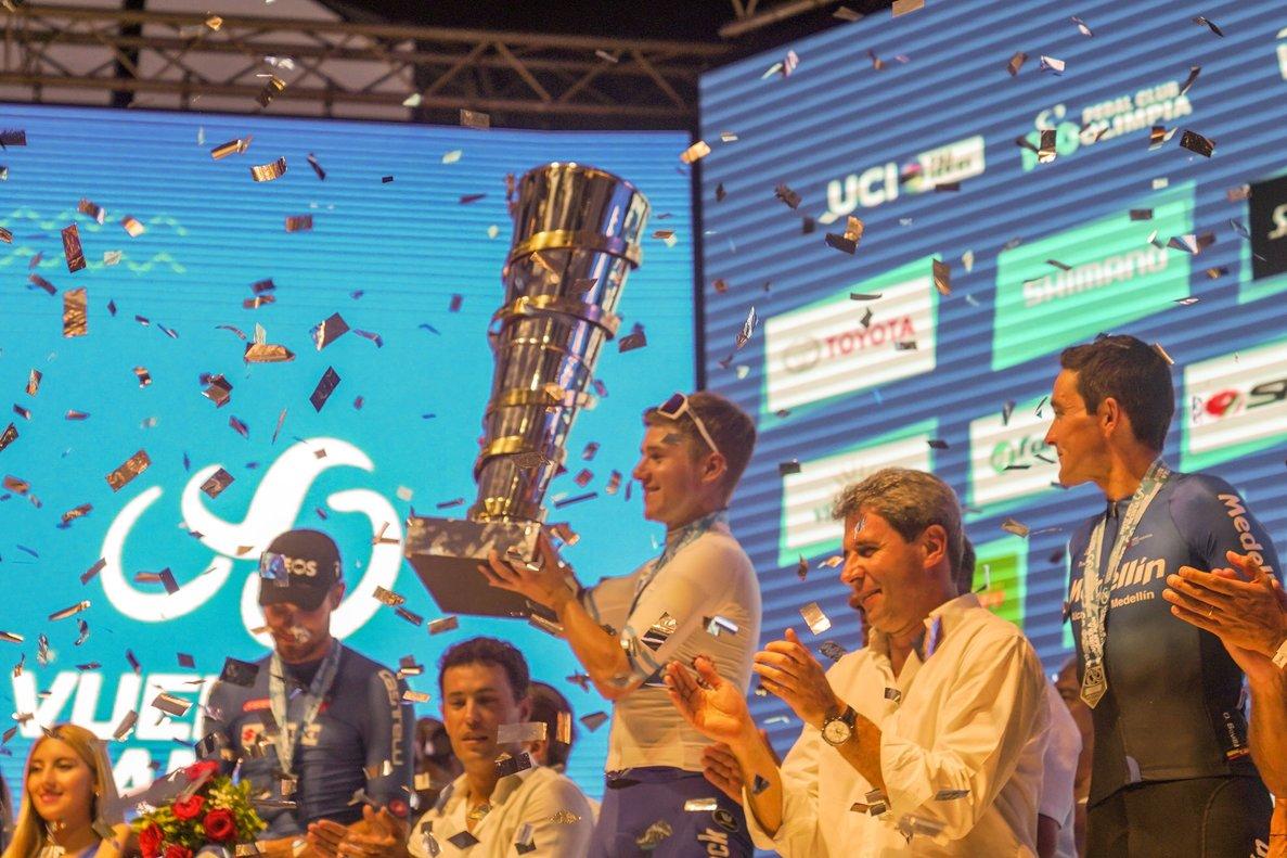 Remco Evenepoel levanta el trofeo en San Juan. Óscar Sevilla, a la derecha.