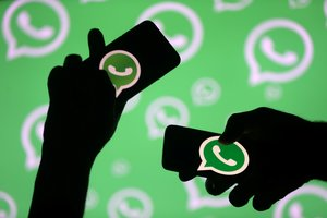 FILE PHOTO: Men pose with smartphones in front of displayed Whatsapp logo in this illustration September 14, 2017. REUTERS/Dado Ruvic/File Photo