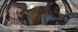 Los dos niños juegan en el interior de un coche abandonado.