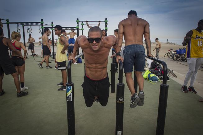 Varios jóvenes se ejercitan en unas barras de la playa de la Barceloneta.