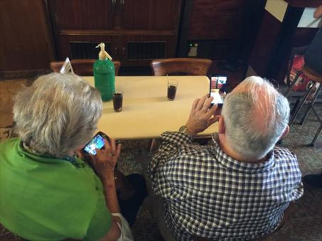 Jubilados consultan sus móviles en un bar.