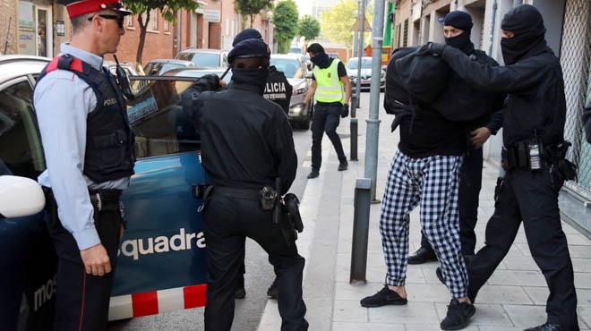 Los Mossos trasladan a uno de los detenidos en la calle Dolors Almeda de Cornellà.