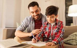 Un padre ayudando a su hijo a hacer los deberes.