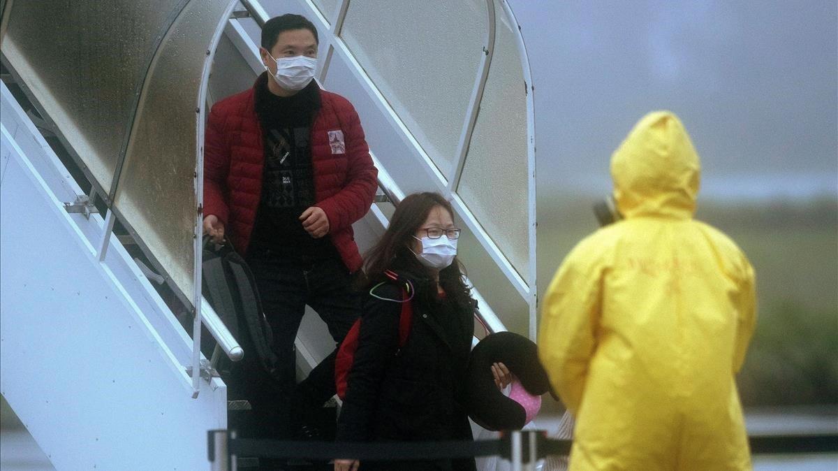 Pasajeros salen de los dos aviones fletados por el Gobierno de Brasil con 34 brasilenos y sus parientes repatriados de la ciudad china de Wuhan, el domingo.