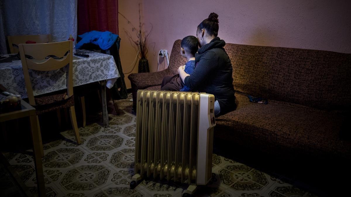Una mujer con uno de sus hijos, víctimas de la pobreza energética, en su piso de Barcelona.