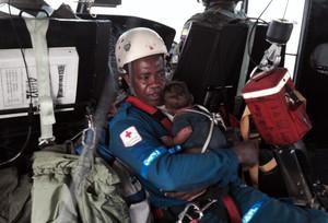 Un integrant de la Creu Roja porta el bebè rescatat després de passar cinc dies perdut amb la seva mare a la selva colombiana.