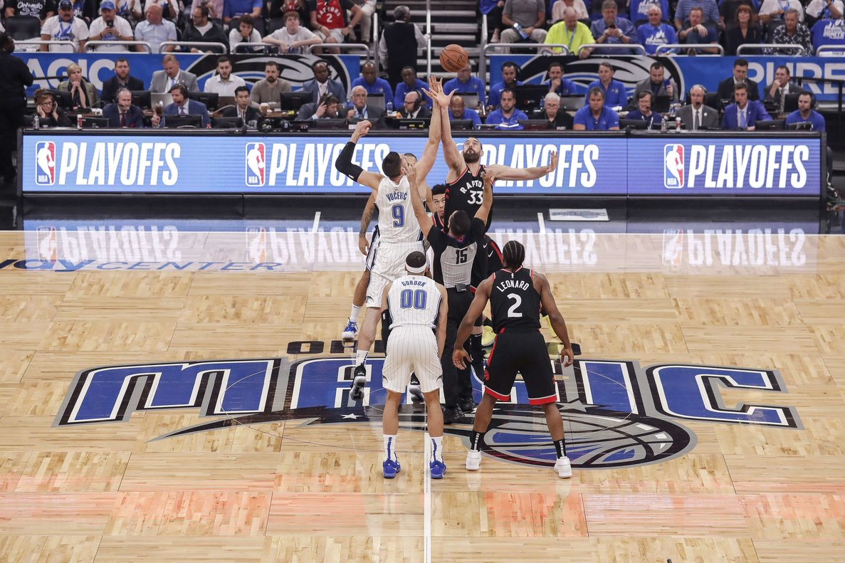 ORLANDO, FL - APRIL 21: Nikola Vucevic #9 of the Orlando Magic goes up against Marc Gasol #33 of the Toronto Raptors on the opening tip off at the start of Game Four of the first round of the 2019 NBA Eastern Conference Playoffs at the Amway Center on April 21, 2019 in Orlando, Florida. The Raptors defeated the Magic 107-85. NOTE TO USER: User expressly acknowledges and agrees that, by downloading and or using this photograph, User is consenting to the terms and conditions of the Getty Images License Agreement. Don Juan Moore/Getty Images/AFP