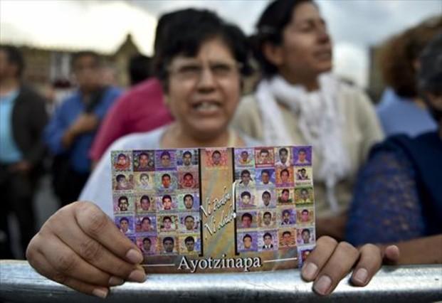 Una mujer muestra la foto de los estudiantes de Ayotzinapa.