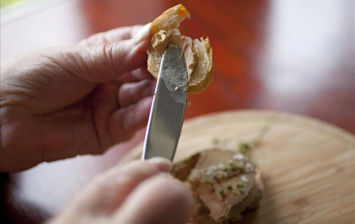 Una mujer se prepara una tostada con foie gras.