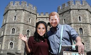 Una pareja con caretas de Meghan y Enrique, ante el castillo de Windsor.