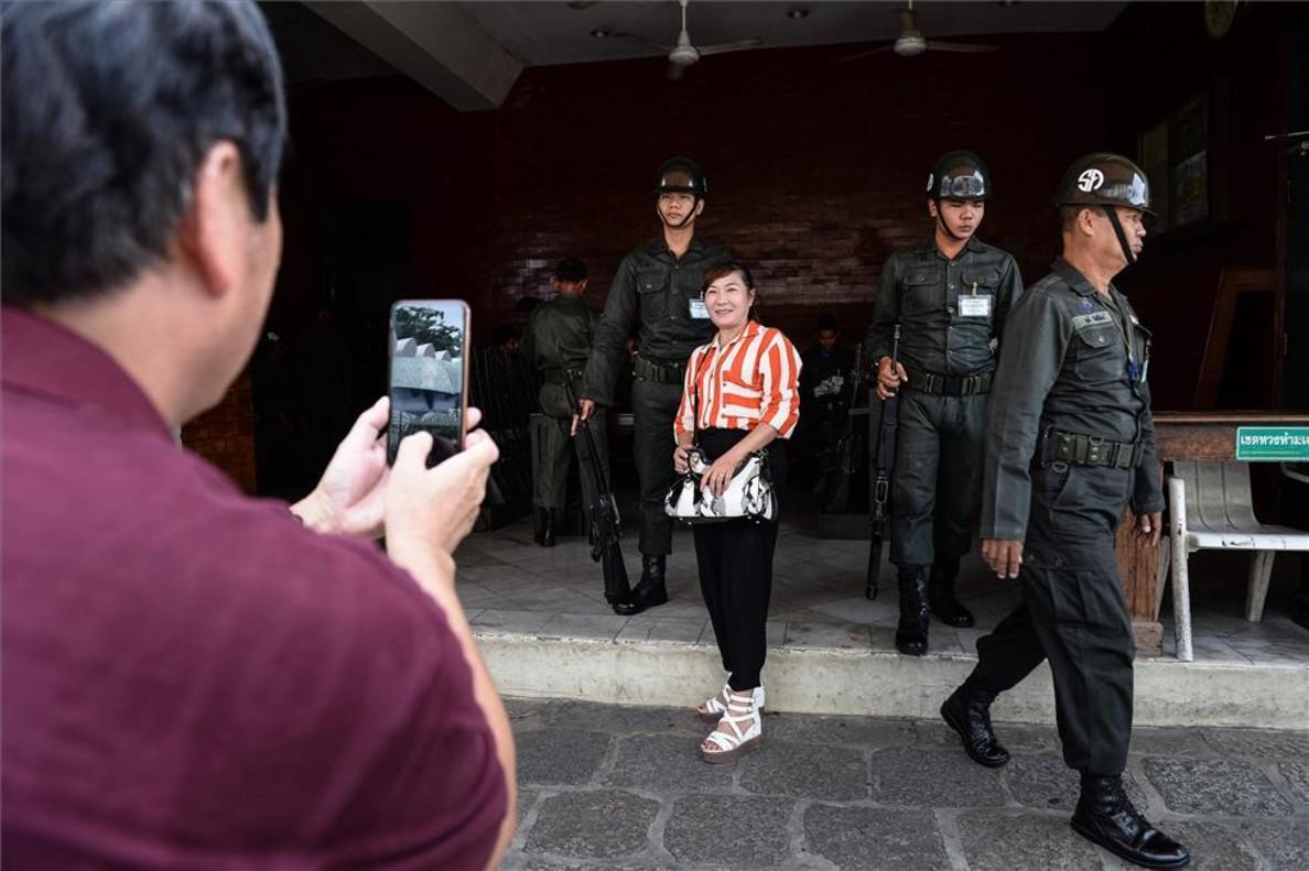 Una turista se fotografía con unos soldados en Bangkok, Tailandia.