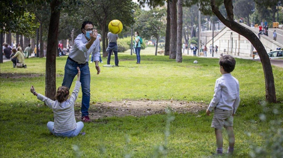 Unos niños juegan con su padre en un parque de Valencia, tras más de un mes encerrados por el coronavirus.