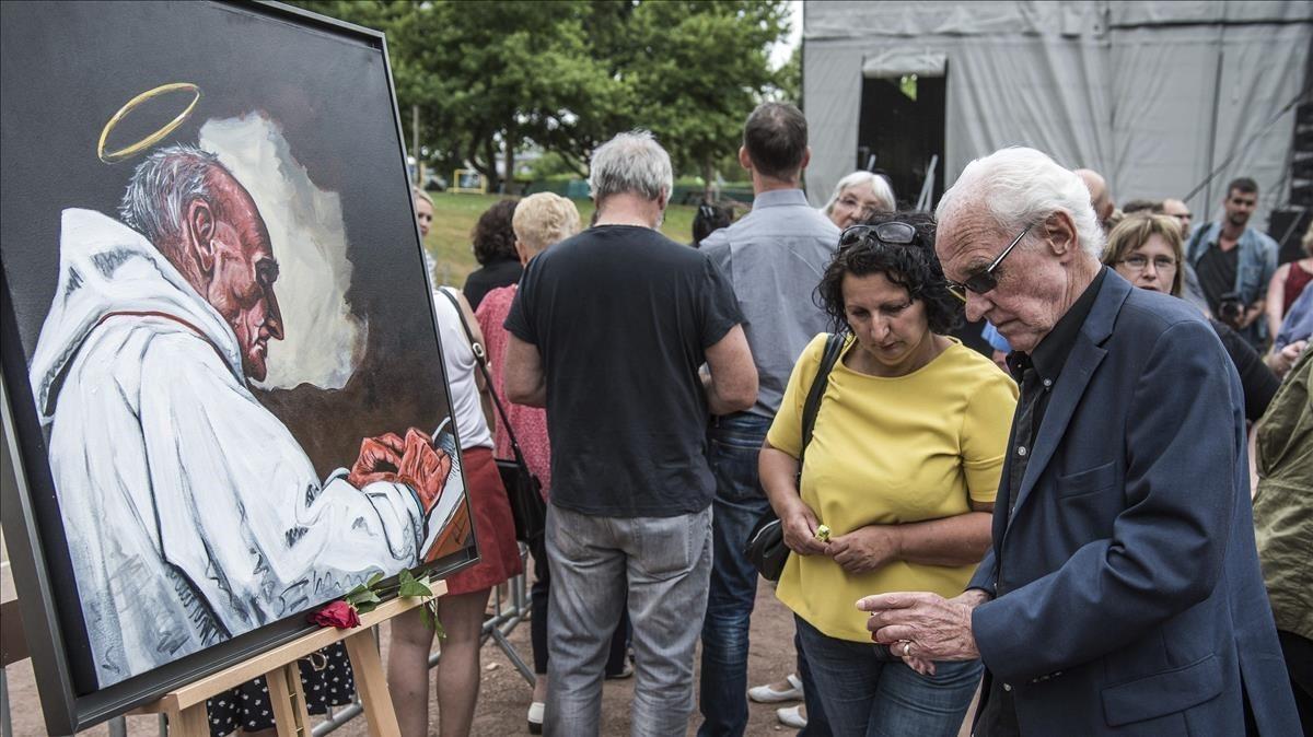 Varios ciudadanos encienden velas delante de un retrato del cura Jacques Hamel,asesinado en un atentado yihadista en Saint Etienne du Rouvray, en Francia.