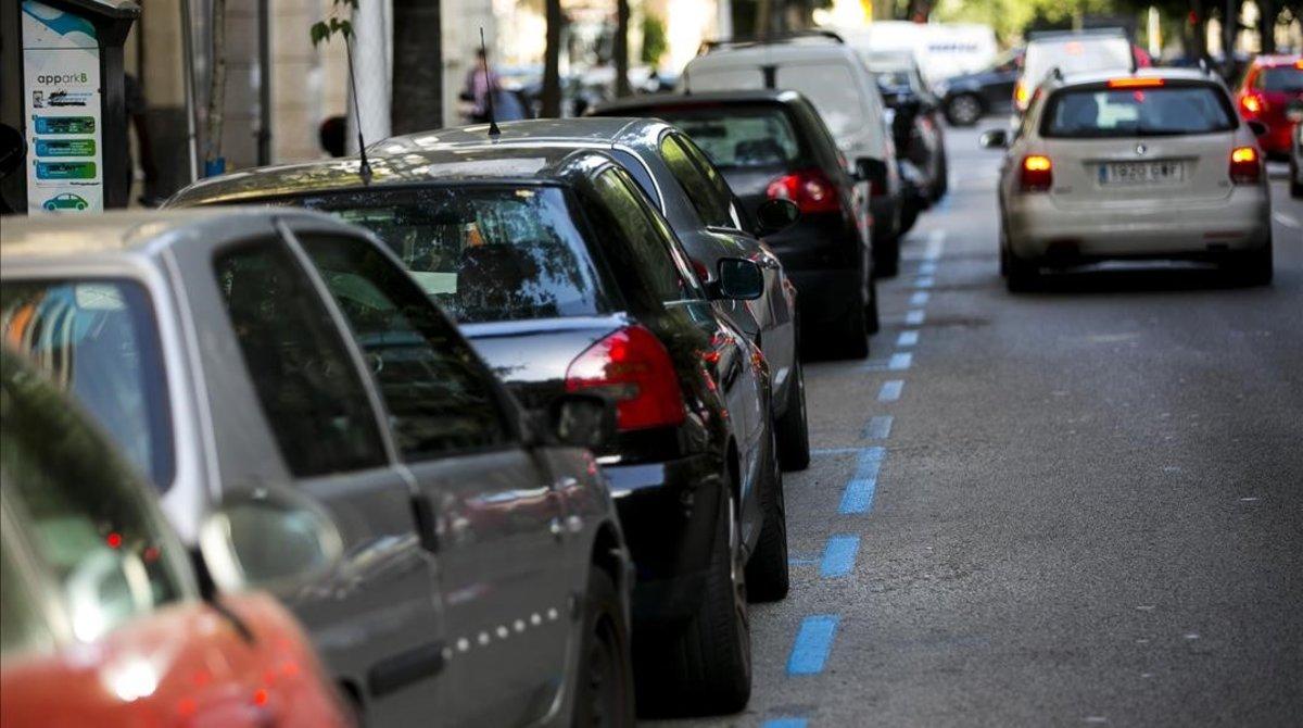 Varios coches estacionados en la zona azul de Barcelona.