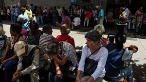 Un grupo de venezolanos hacen cola frente a un banco de Caracas para cobrar sus pensiones.