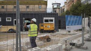 Un operario trabaja en la instalación de unos módulos prefabricados en una nueva escuela de Barcelona.