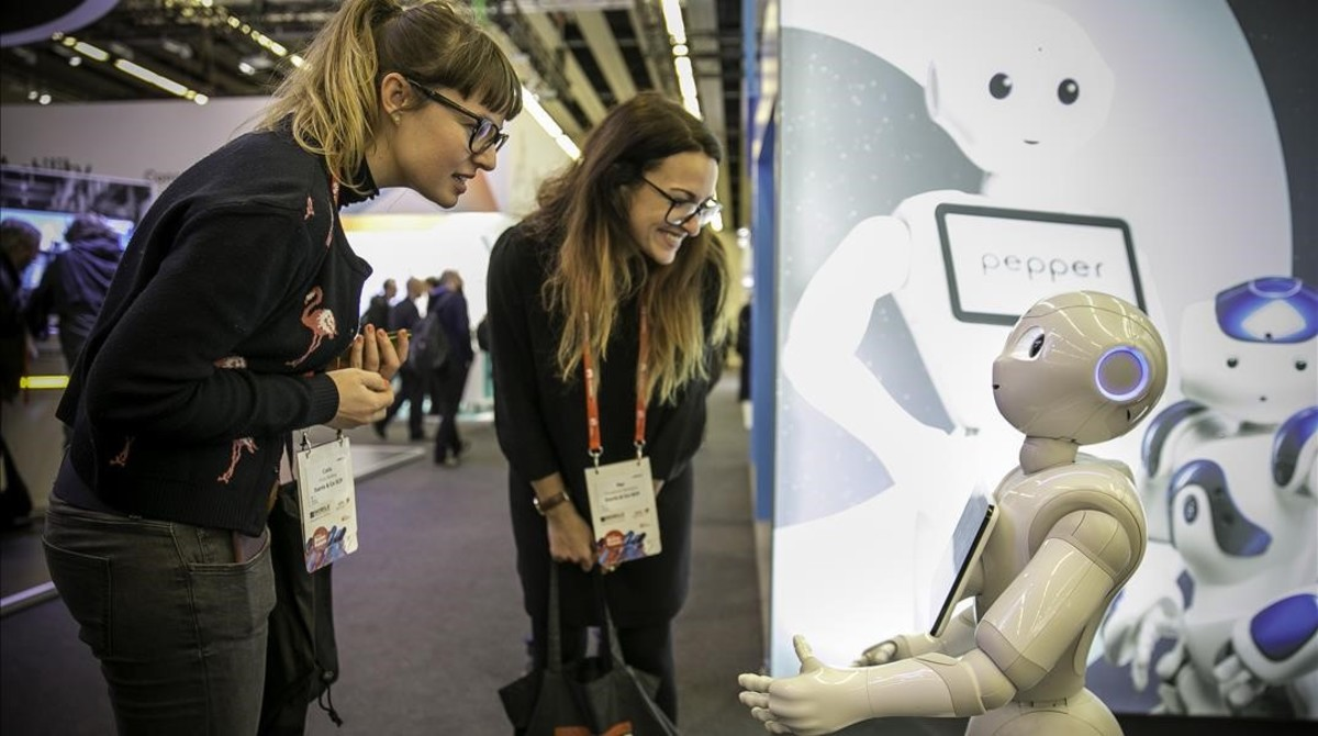 Dos mujeres hablan con un robot en el Mobile World Congress.