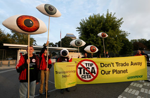 Greenpeace activists hold banners and giant eyes during a demonstration against the trade agreements TTIP, CETA and TiSA in front of the U.S. Mission in Geneva