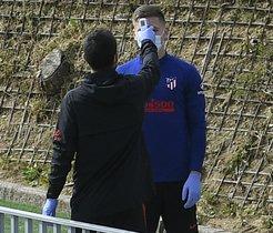 Un operario del Atlético de Madrid le hace un control de temperatura a un jugador antes de entrenar.