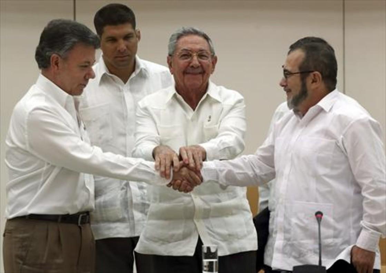 El presidente de Cuba, Raúl Castro, aprieta las manosde Juan Manuel Santos (izquierda) y 'Timochenko', en La Habana.