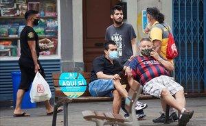 Un agente cívico informa a un ciudadano del uso de la mascarilla en el barrio de la Torrassa, en L'Hospitalet.