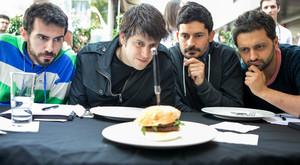 Los cuatro integrantes de la banda Els Amics de les Arts observan la hamburguesa que lleva su nombre.