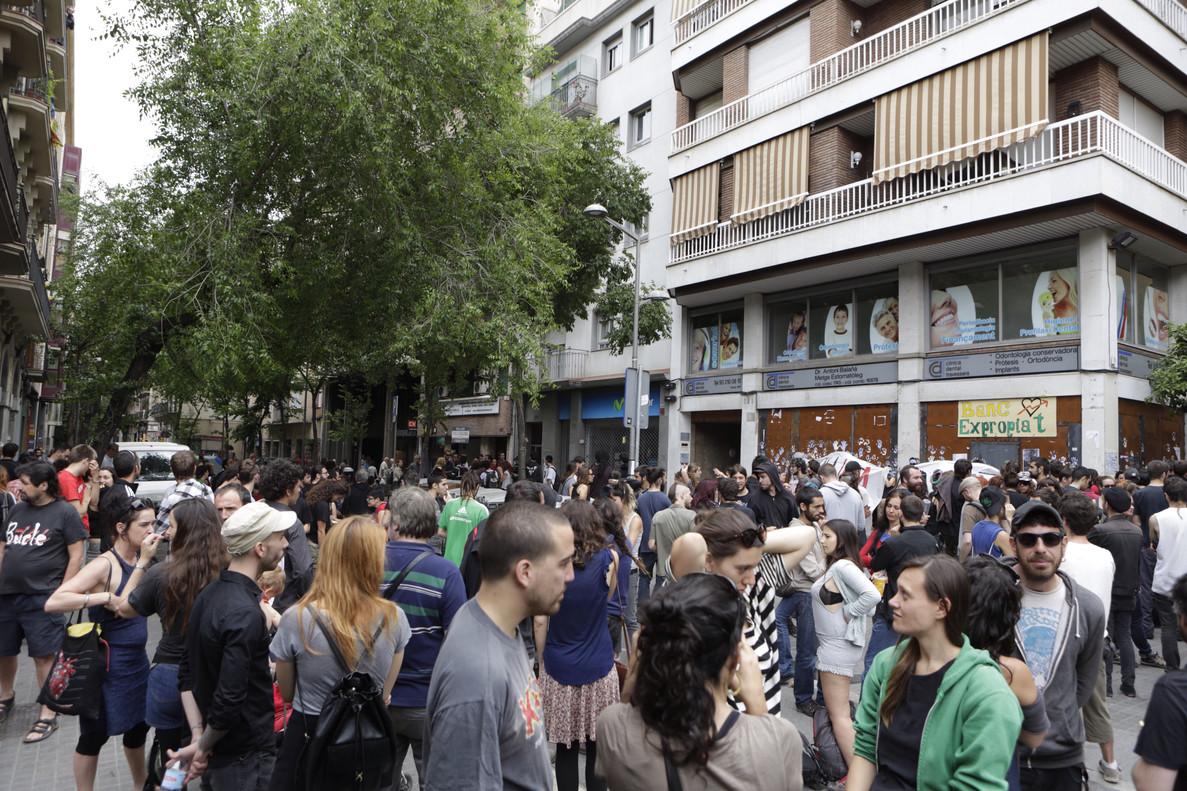 Concentración de personas antes las puertas del 'banco expropiado' de Gràcia, antes de la llegada de los Mossos.