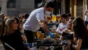 Un camarero sirve a sus clientes en un bar de la plaça de la Font de Tarragona.