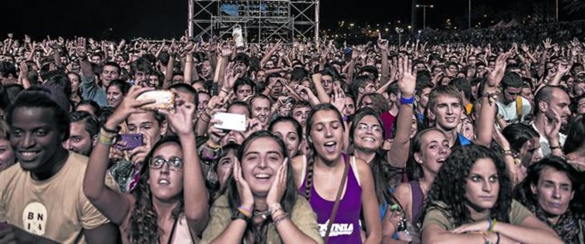 Centenares de jóvenes abarrotan la playa del Bogatell, durante un concierto de verano con motivo de las fiestas de la Mercè.