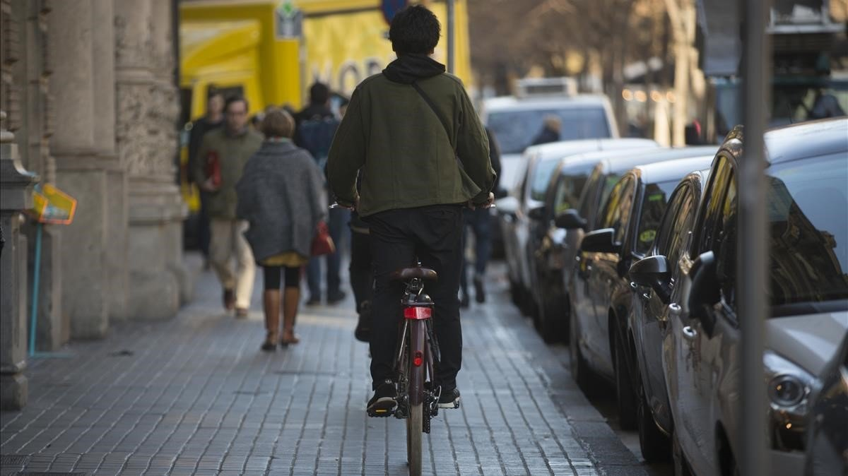 Un ciclistaen la acera de la Rambla de Catalunya