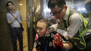 El concejal de distrito Andrew Chiu recibe asistencia sanitaria tras sufrir una agresión en un centro comercial de Hong Kong, este domingo.