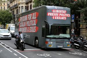 El bus de Òmnium,con lema libertad presos políticosen inglés y castellano, ante la sede de la entidad en Barcelona.