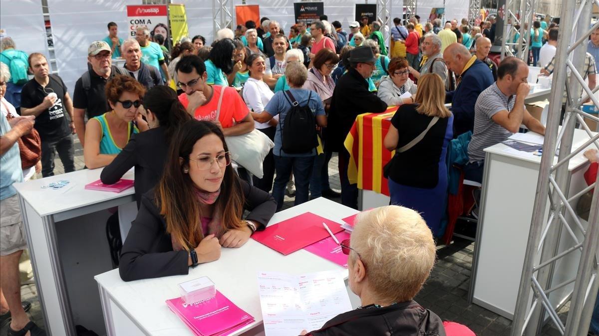 Diversas personas solicitando información en el espacio 'Eines de País', ubicado en el Pla de Palau.